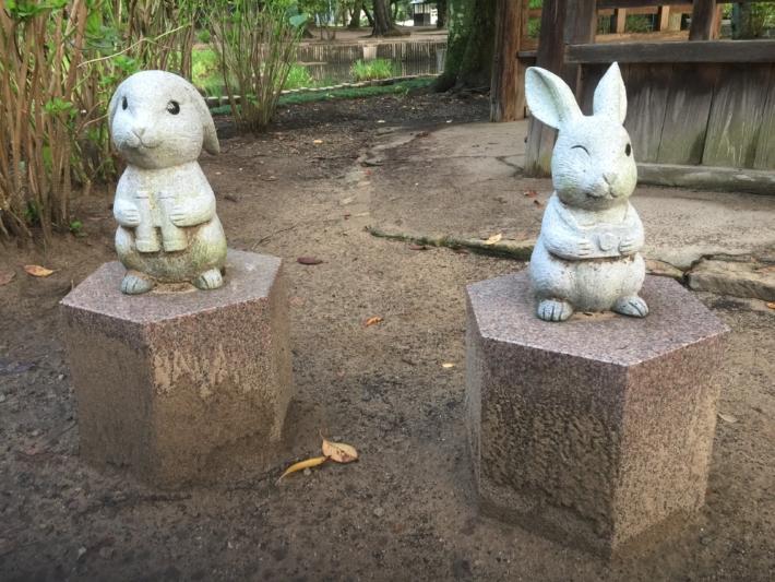 双眼鏡とカメラを持って池を見るウサギ像