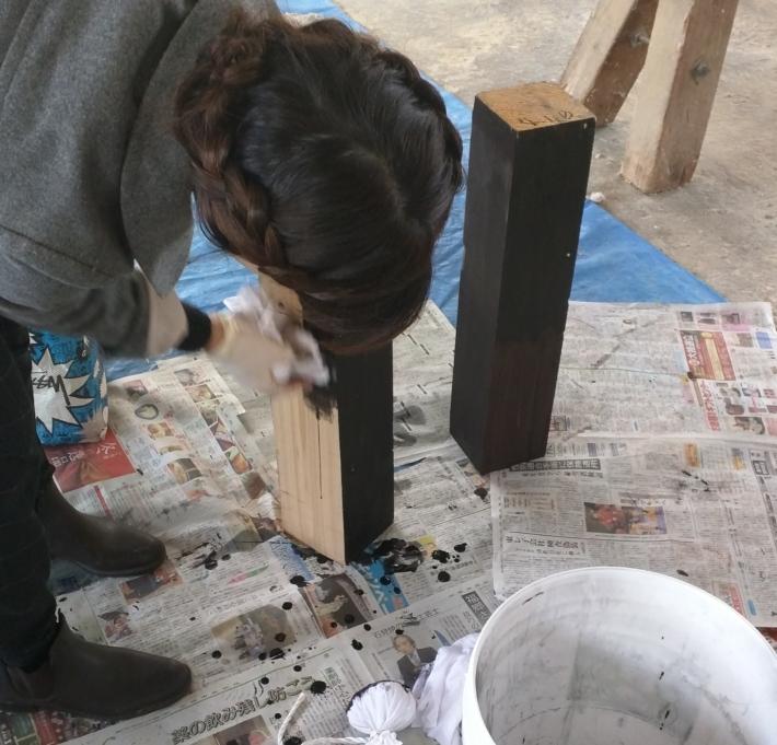 ペンキで木材を塗る様子